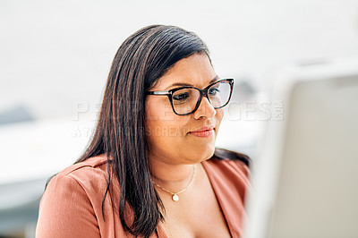 Buy stock photo Cropped shot of an attractive young businesswoman sitting alone in her office and using her computer