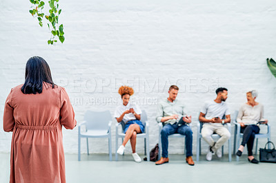 Buy stock photo Full length shot of a diverse group of businesspeople sitting together while waiting for their interviewer in the office