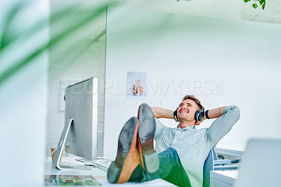 Buy stock photo Cropped shot of a handsome young businessman sitting with his hands behind his head and feet up in his office