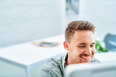 Buy stock photo Cropped shot of a handsome young businessman sitting alone in his office and using his computer