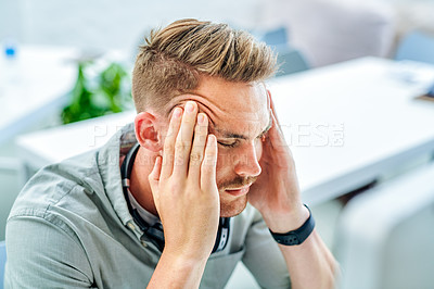 Buy stock photo Cropped shot of a handsome young businessman sitting in his office and suffering from a headache while using his computer