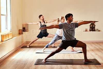 Buy stock photo Shot of a group of young men and women practicing the warrior pose pose during a yoga session