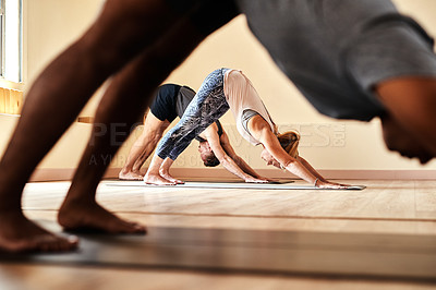 Buy stock photo Shot of a group of young men and women practicing the downward facing dog pose during a yoga session