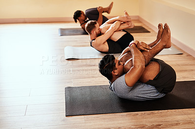 Buy stock photo Shot of a group of young men and women practicing yoga in a fitness class
