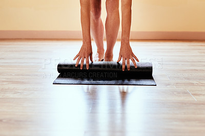 Buy stock photo Cropped shot of a woman rolling out her yoga mat