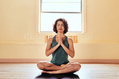 Buy stock photo Shot of a young woman meditating during a yoga session