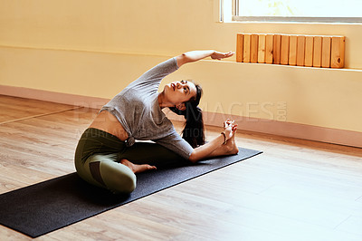 Buy stock photo Shot of a young woman stretching during a yoga session