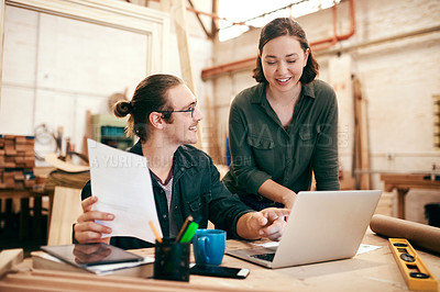 Buy stock photo Cropped shot of two young carpenters planning and working on a laptop together inside their workshop