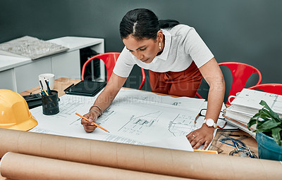 Buy stock photo Shot of a young architect working with blueprints in an office