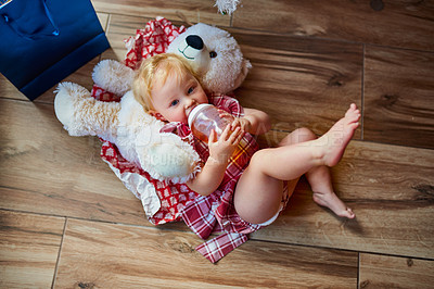 Buy stock photo High angle shot of an adorable baby girl drinking out her bottle while lying down on the floor at home
