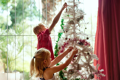 Buy stock photo Shot of two adorable young siblings decorating a Christmas tree together at home