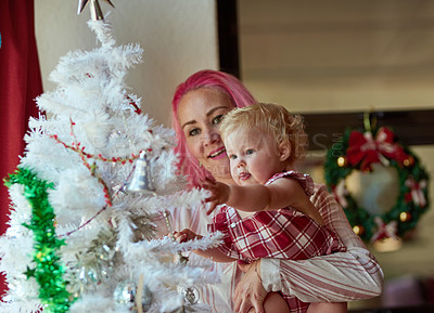 Buy stock photo Shot of an adorable baby girl decorating a Christmas tree with her mother at home