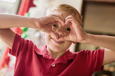 Buy stock photo Shot of an adorable little boy doing making a heart shape with his hands at home