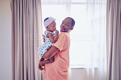 Buy stock photo Shot of an adorable baby girl bonding with her father at home