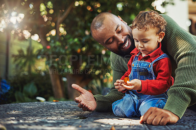 Buy stock photo Cropped shot of a handsome young man bonding with his adorable son during a day out