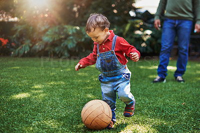 Buy stock photo Cropped shot of an adorable little boy playing with a ball while bonding with his father outdoors