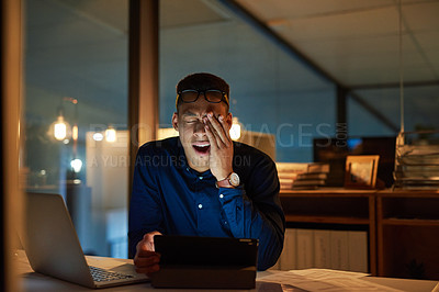 Buy stock photo Shot of a young businessman feeling exhausted during a late night at work