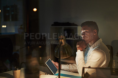 Buy stock photo Shot of a young businessman looking thoughtful while using a digital tablet during a late night at work