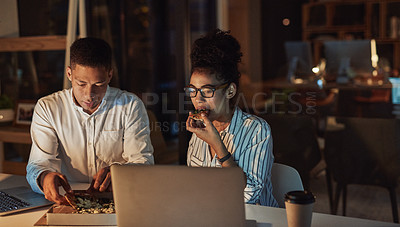 Buy stock photo Shot of a young businessman and businesswoman having pizza during a late night meeting at work