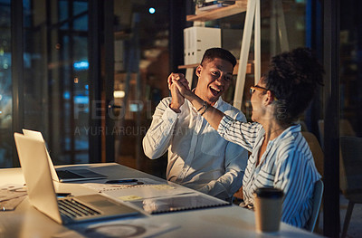 Buy stock photo Shot of a young businessman and businesswoman giving each other a high five during a late night meeting