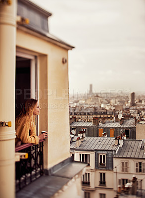 Buy stock photo Cropped shot of an attractive young woman leaning on a French balcony and holding a cup of coffee