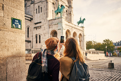 Buy stock photo Cropped shot of an unrecognizable couple standing together and using a cellphone to take pictures while sightseeing in Paris