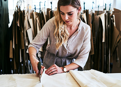 Buy stock photo Cropped shot of a young fashion designer cutting fabric in her workshop