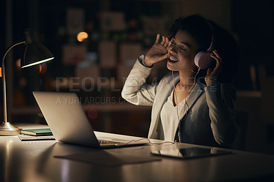 Buy stock photo Cropped shot of an attractive young businesswoman listening to music and working on a laptop inside her office at night