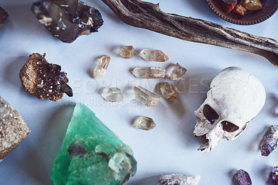 Buy stock photo High angle shot of a table filled with different types of crystals and a skull inside during the day