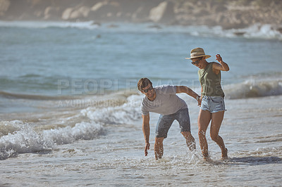 Buy stock photo Shot of a happy young couple having fun in the water at the beach
