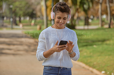 Buy stock photo Shot of a happy young woman listening to music and using a smartphone in the park