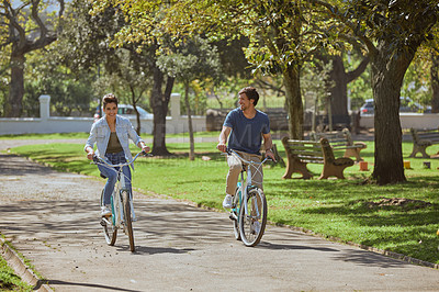 Buy stock photo Shot of a happy young couple going for a bicycle ride in the park