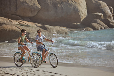 Buy stock photo Shot of a happy young couple going for a bicycle ride along the beach