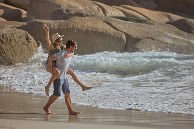 Buy stock photo Shot of a happy young couple enjoying a piggyback ride at the beach