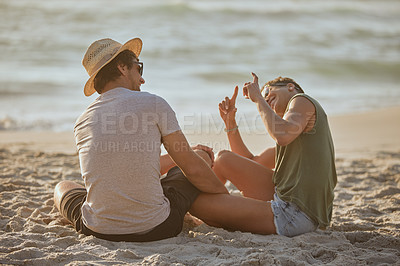 Buy stock photo Rearview shot of a happy young couple sharing a playful moment on the beach at sunset