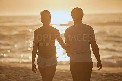 Buy stock photo Rearview shot of a young couple watching the sunset at the beach