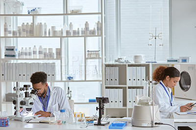 Buy stock photo Shot of two young scientists working in a lab