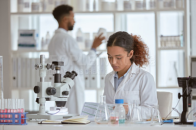 Buy stock photo Shot of a young scientist working in a lab with a colleague in the background