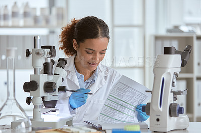 Buy stock photo Shot of a young scientist going through paperwork in a lab