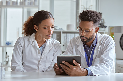 Buy stock photo Shot of two young scientists using a digital tablet while working together in a lab
