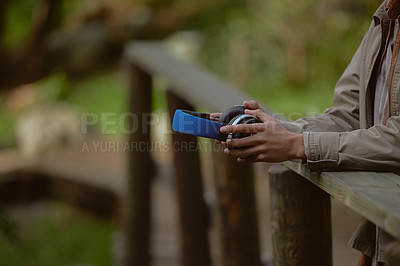 Buy stock photo Cropped shot of an unrecognizable man standing alone and holding his headphones during a day out in the forest