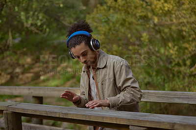 Buy stock photo Cropped shot of a handsome young man standing alone and listening to music through his headphones in the forest