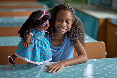 Buy stock photo Shot of a young girl playing with a doll in a classroom at school