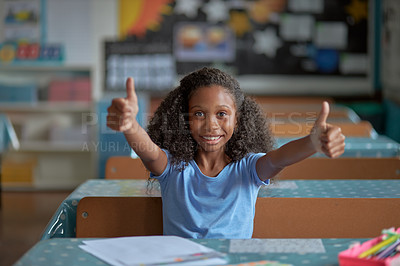 Buy stock photo Portrait of a happy young girl giving thumbs up while sitting at her desk in a classroom