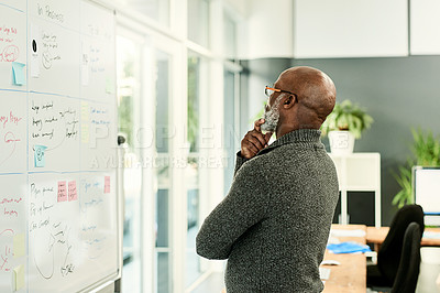 Buy stock photo Cropped shot of a handsome mature businessman standing alone and looking contemplative while reading a white board in the office
