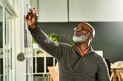 Buy stock photo Cropped shot of a handsome mature businessman standing alone and writing on a white board in the office