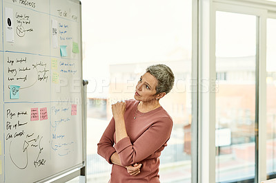 Buy stock photo Cropped shot of an attractive  businesswoman standing alone and looking contemplative while reading a white board in the office