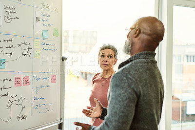 Buy stock photo Cropped shot of two mature businesspeople standing together and using a white board during a discussion in the office
