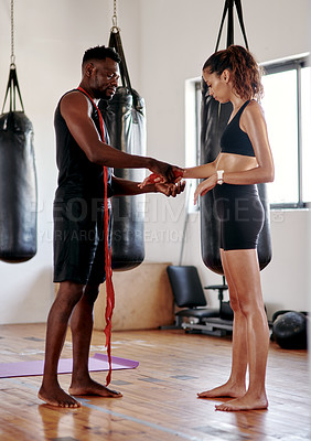 Buy stock photo Full length shot of an attractive young female boxer getting her hands wrapped by her fitness coach in a gym