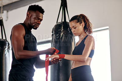 Buy stock photo Cropped shot of an attractive young female boxer getting her hands wrapped by her fitness coach in a gym